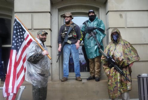Four men carrying arms and an American flag in front of the Michigan State Capital building.