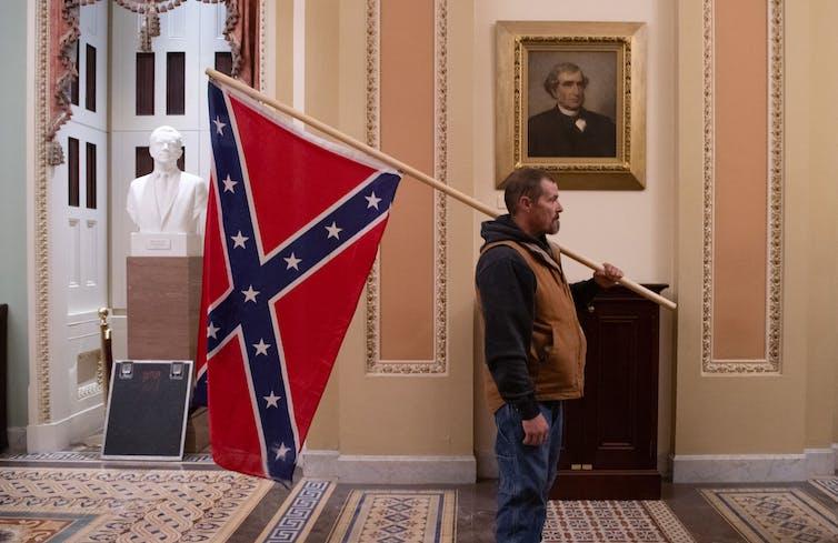 Un partisan du président Donald Trump tient un drapeau confédéré devant la salle du Sénat.