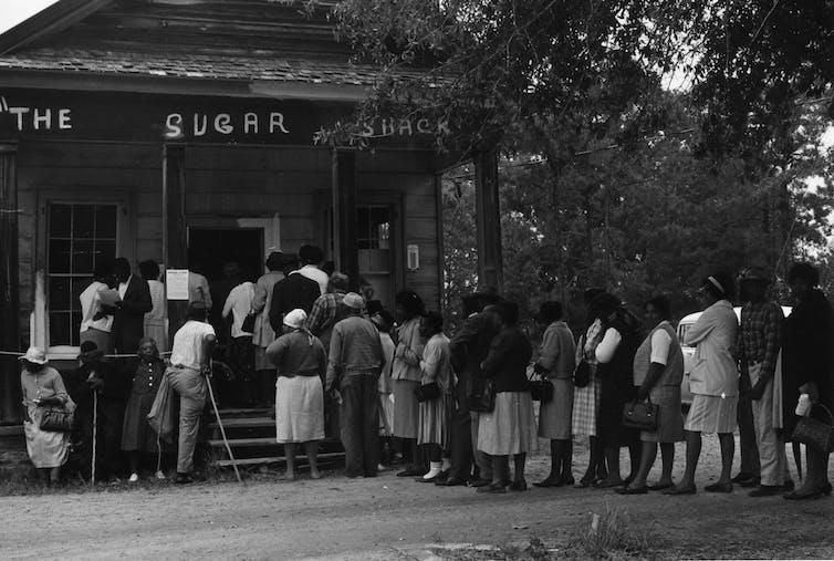 Un groupe d'électeurs fait la queue devant un bureau de vote, une petite boutique dans la cabane à sucre, à Peachtree, Alabama, en 1966.