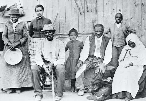 Harriet Tubman poses with a group of Black adults and children who she helped free from slavery.