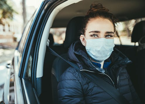 A woman wearing a medical mask looks out of an open driver's window of a car.