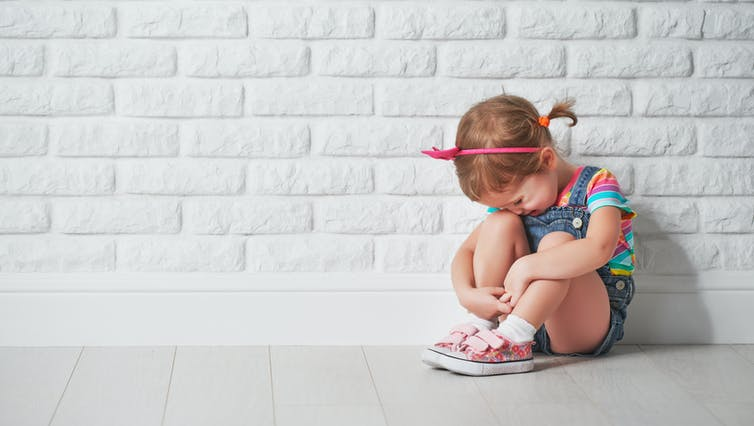 A little girl having a tantrum sits against a white brick wall.