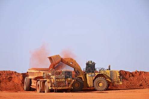 Mining site, red dust, trucks