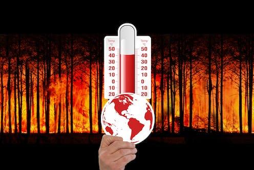 Tangan memegang globe dan termometer dengan latar belakan gambar hutan terbakar.