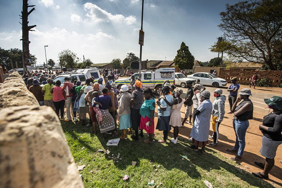 People standing in a line alongside a road