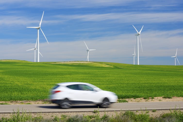 A car drives past a field with wind turbines