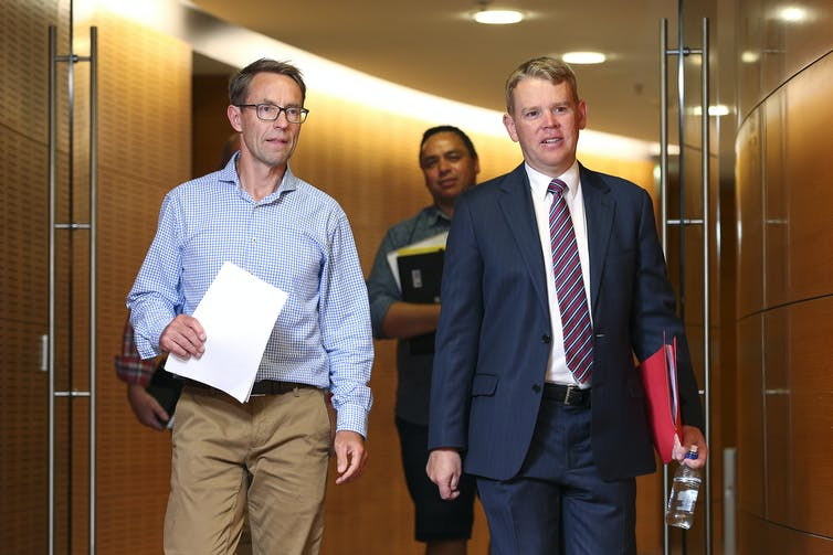 Ashley Bloomfield and Chris Hipkins walking in parliament corridor