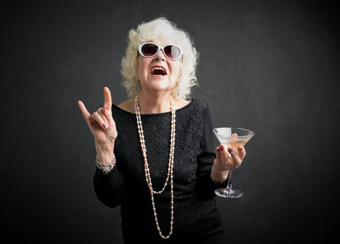 Grandma with glasses and drink in hand showing rock sign