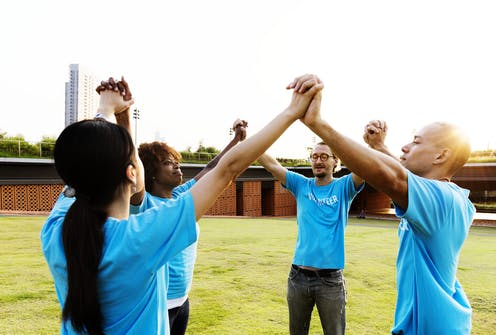 People wearing blue volunteer T-shirts join hands.