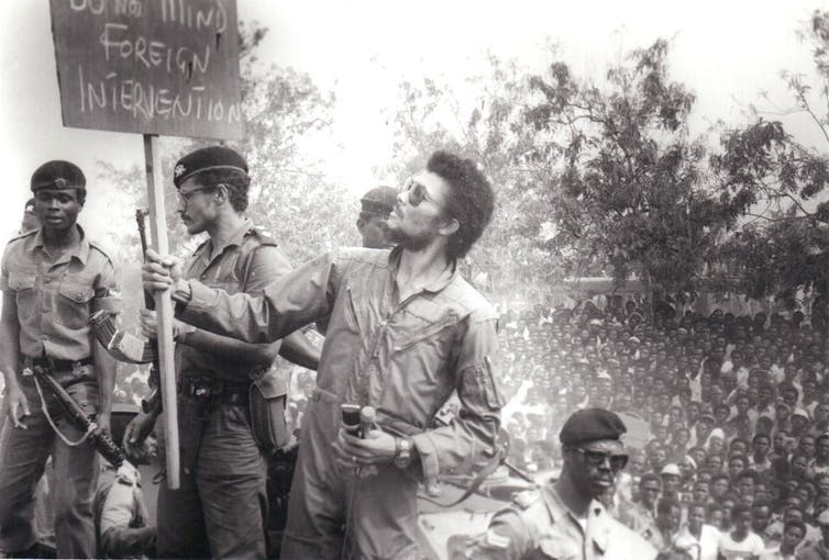 A man in an overall and shades reads a placard that says, 'Do Not Mind Foreign Intervention', a crowd of peoplein the background.