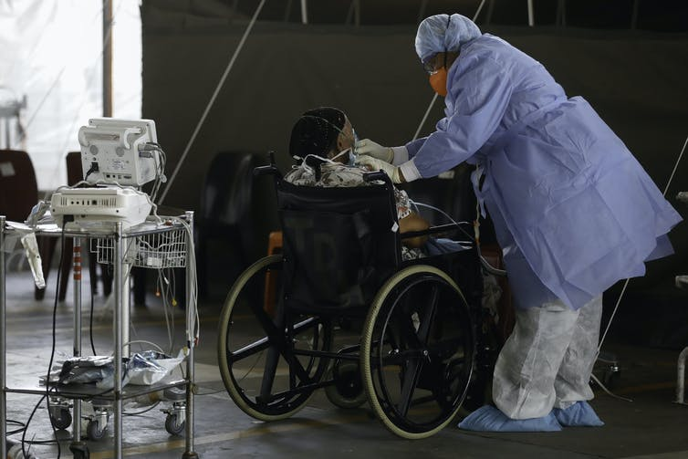 A healthcare worker stands next to a patient at a temporary ward in a South African hospital