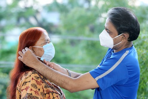 Man putting on face mask for older woman