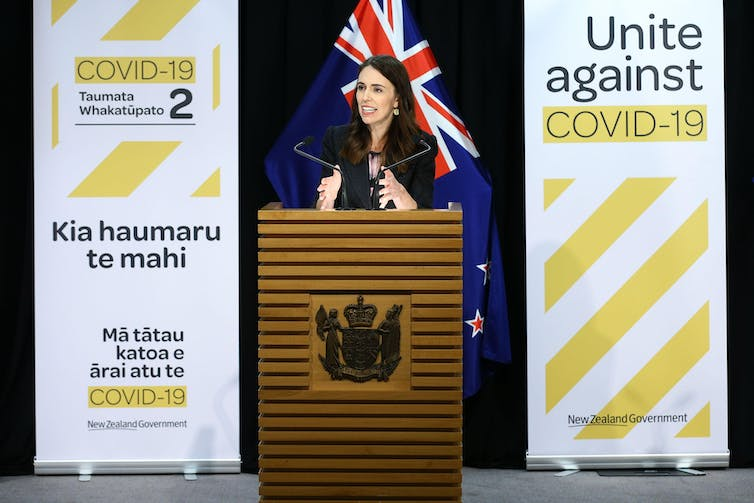 Jacinda Ardern standing behind podium between two COVID-19 health campaign banners