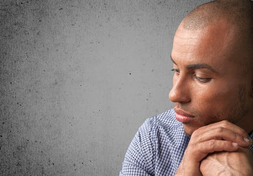Profile of a pensive man with his cheek resting on his clutched hands