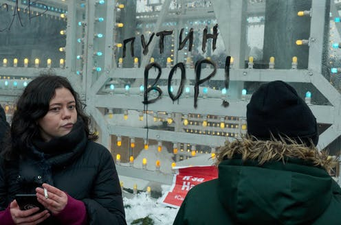 A woman holds a cigarette and a mobile phone in front of a message on a window in Cyrillic lettering which reads: 'Putin is a thief'.