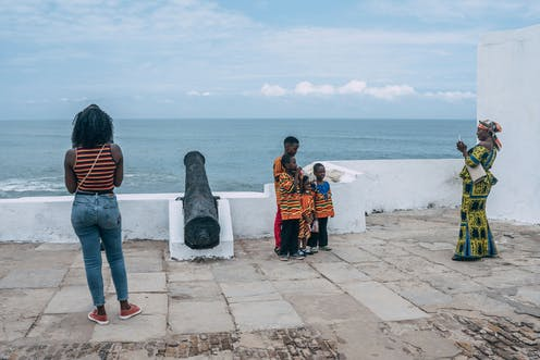 In front of a view of the sea from a fort with a cannon, a woman in traditional attire takes a photo of four children.