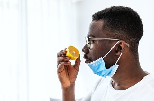 A man sniffs an orange with his medical mask down.