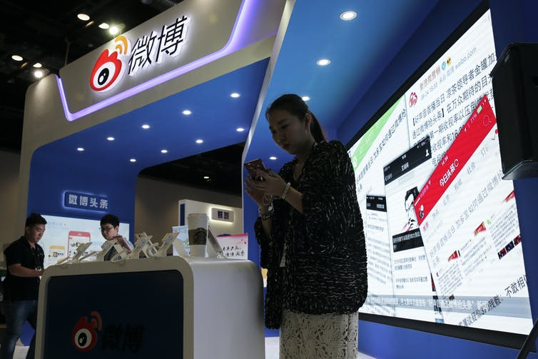 A woman looks at her phone while standing in a tradeshow booth that has a display in Chinese.