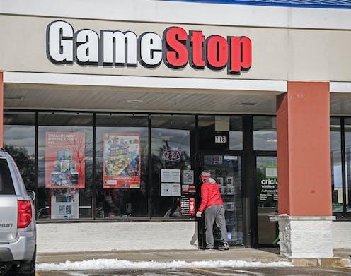 A man walking into a GameStop store.