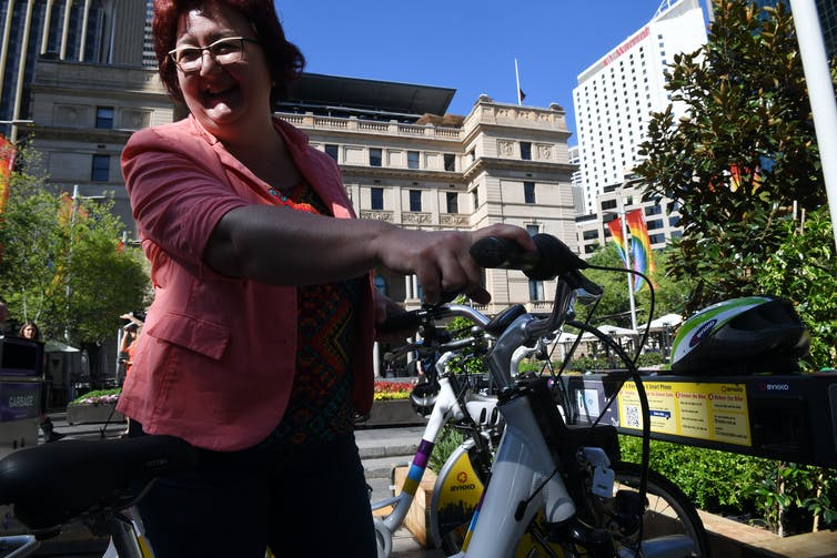 Women takes an e-bike from a stand