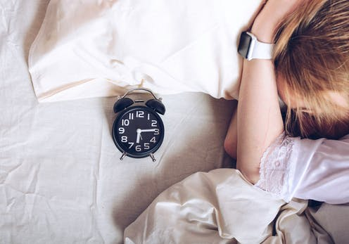 girl in bed with alarm clock, watch on