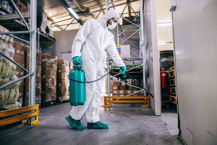 Man in a protective suit and mask disinfecting warehouse full of food products.