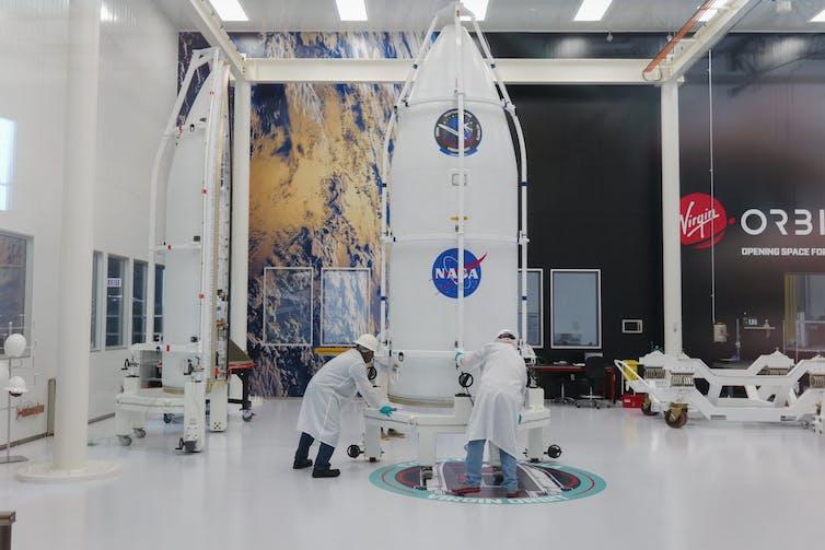 La charge utile de la NASA dans un entrepôt est inspectée par deux hommes.