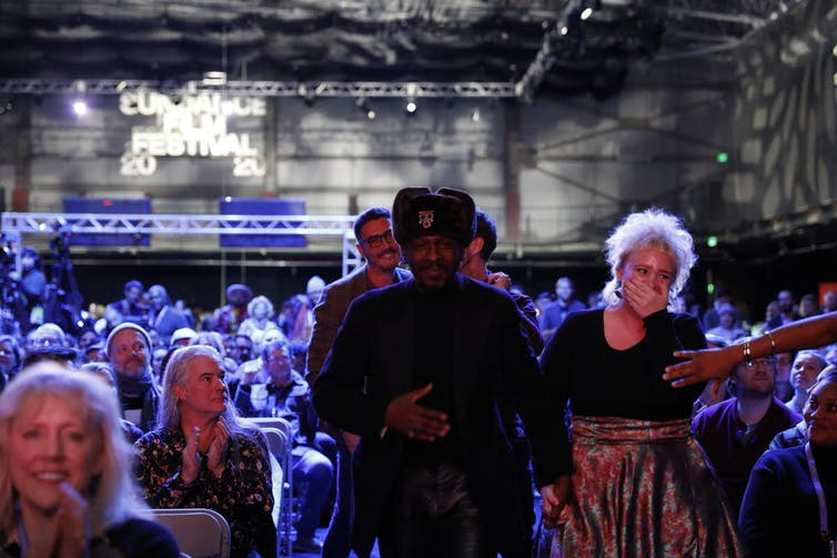 A glitzy room full of people, a man and a woman heading to stage, he in a hat and jacket, she in a full skirt and clutching her mouth in surprise.