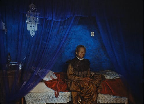An elderly woman sits on a bed, dressed in a formal vintage gold dress against a backdrop of blue curtains and walls.