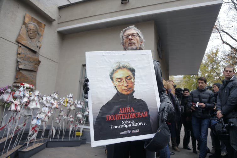 A man holds up a poster with a picture of Russian journalist Anna Politkovskaya, who was murdered in 2006.