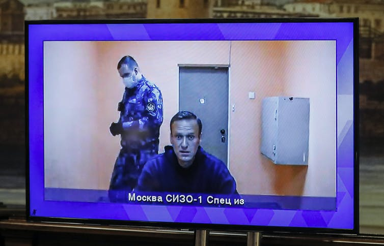 Video monitor showing Russian opposition activist Alexei Navalny in a jail cell with a Russian prison guard in the background.