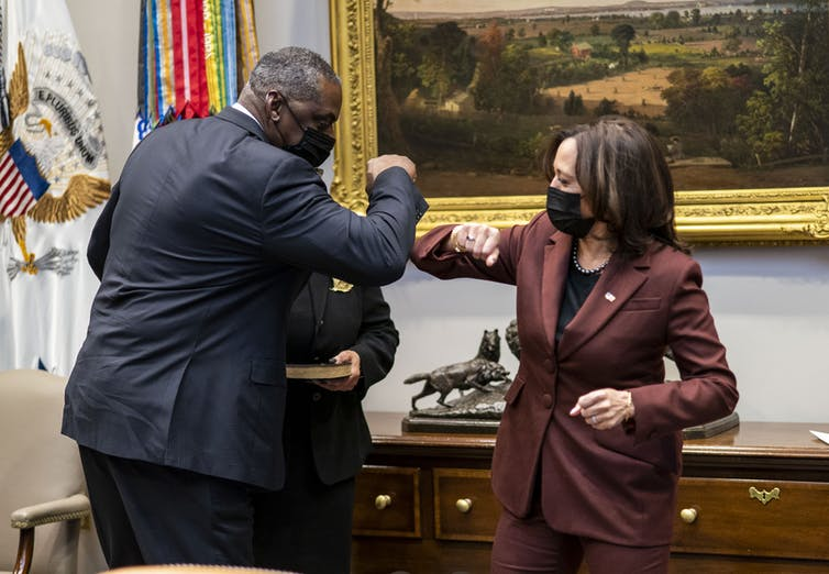 Vice President Kamala Harris and Secretary of Defense Lloyd Austin elbow bump.