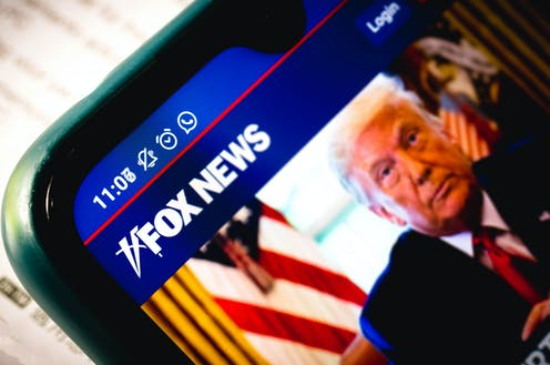 A close-up of a smartphone shows a Fox News article accompanied by an image of Donald Trump.