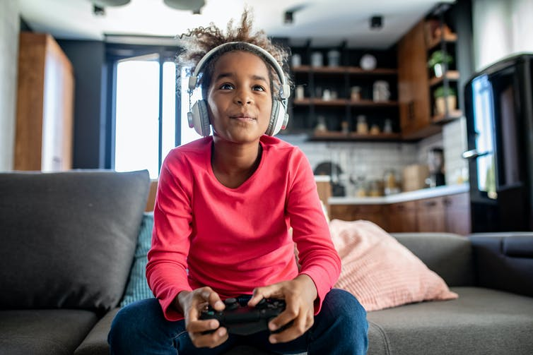 A lively engaged girl sits on a couch playing video games.