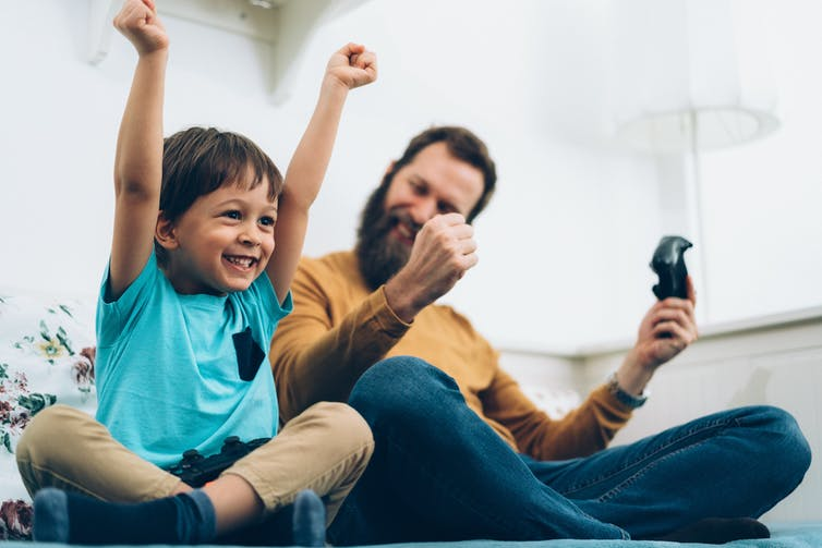 A father and son playing a video game together cheer in victory.