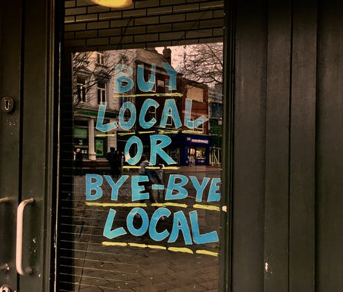 A storefront with a sign that reads Buy Local or Bye-Bye Local.