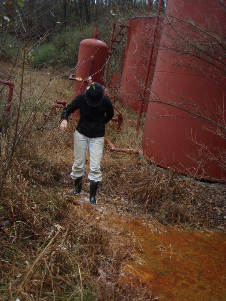 A woman walks through an oil spill near tanks.