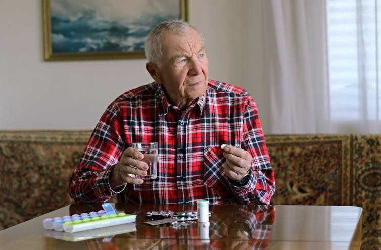 A senior man taking a tablet. There are a variety of medications on the table.