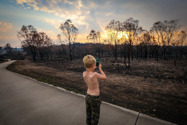 Boy takes photo of burnt bush