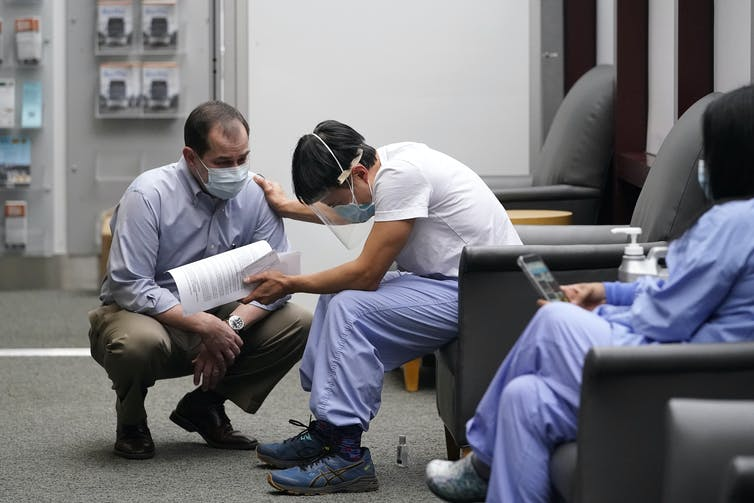 A man in scrubs and a face shield reaches out to a man in a face mask.