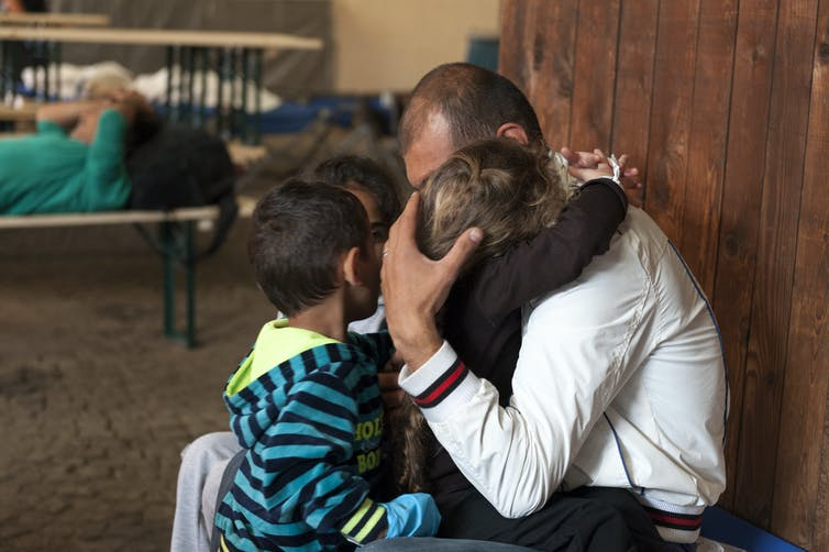 Man hugging three small children at asylum centre