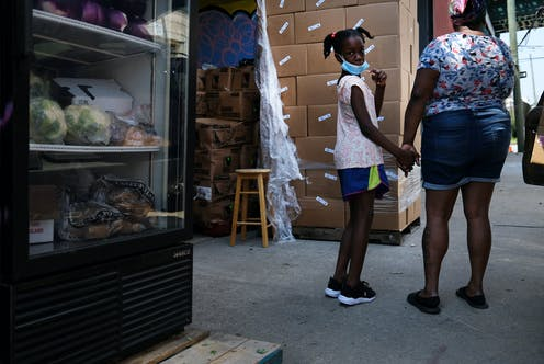 A mother and daughter wait for assistance at a decentralized food hub in New York City.