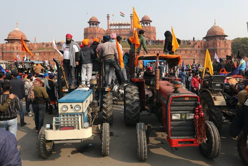 Men with flags stand on two tractors overlooking Delhi's Red Fort