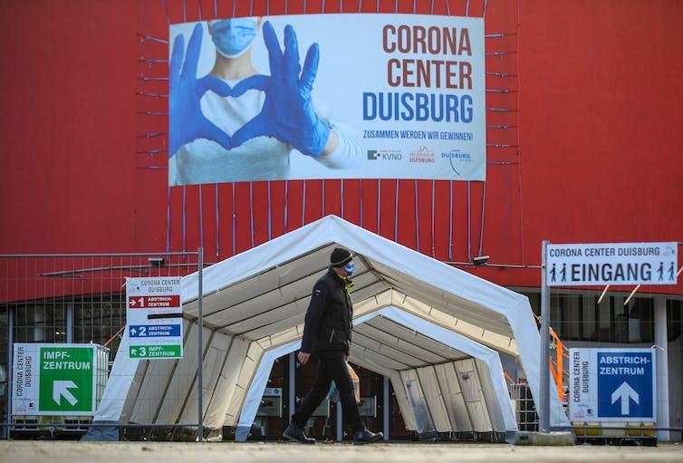 A man walks past a coronavirus vaccine distribution centre.