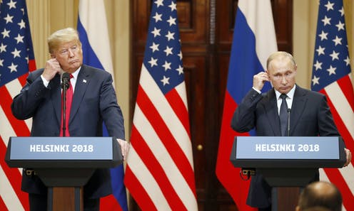 US president Donald Trump (right) and Vladimir Putin at a press conference in Helsinki in 2018. They are both standing at podiums and adjusting their earpieces with Russian and US flags inthe background.