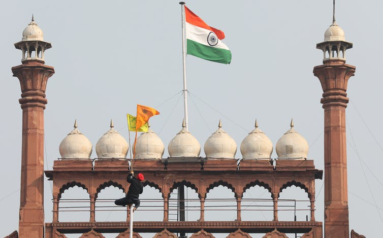 A man climbs a flag pole to raise a yellow and orange flag in front on Delhi's Red Fort and the Indian national flag