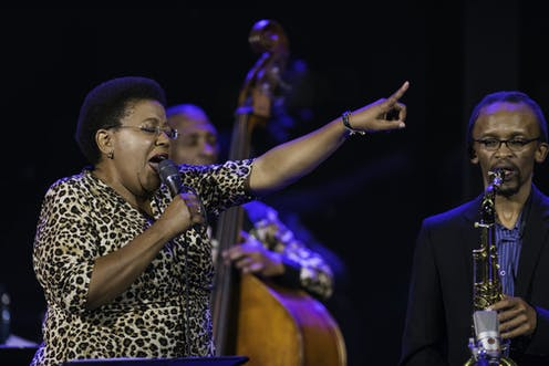 A woman in a leopard print dress and short Afro hairstyle closes her eyes as she sings into a microphone, her finger pointing in the air ahead of her. Around her are jazz musicians playing live.