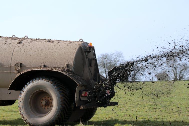 A truck distributes manure on a farmer's field.
