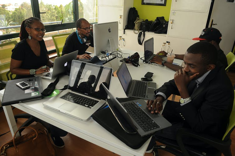 Four young Kenyans sit at a table with computers