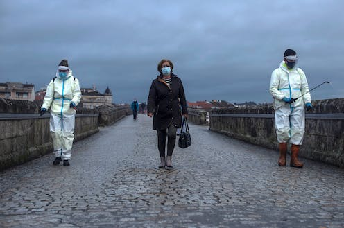 A woman crosses the Roman Bridge in Galicia, Spain, as local workers disinfect it